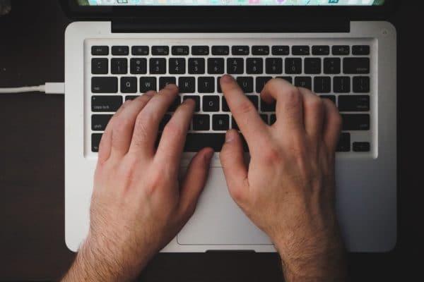 Man's hands on laptop keyboard